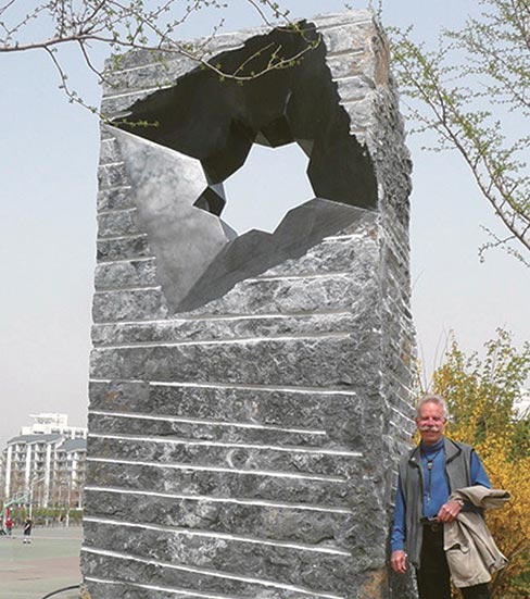 "A smiling Jon Hudson leans against his ""Synchronicity Beijing."" This commision was carved in 2011 to commemorate the 100th anniversary of Tsinghai University, Beijing, China, founded with assistance from the U.S.A.. Erected on the campus, it is a towering 16 feet tall, 8 feet wide and 2 feet deep."