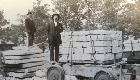 "A day's worth of blocks and slabs ready for transport. Judging by their more formal clothing, these men are likely quarry owners or supervisors rather than quarry workers. ""Initially, the quarries were shipping their stone by canal, but when the railroads came in, around the 1850s, the stone was also being shipped by rail,"" explained Barbara Newberg. Note the hoist chains on this mini flat car of trimmed stone."