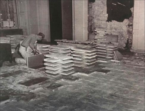 Restoration in progress of the Joliet limestone flooring installed in the White House. This archive photo shows a  stone mason removing the flooring slabs in the North-East corner of the White House main entrance lobby.