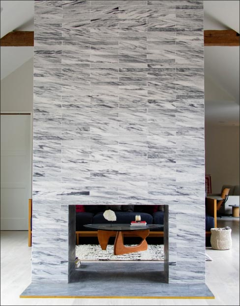 Custom cut tiles of Pearl Grey marble are laid in horizontal courses to achieve an avant garde style.