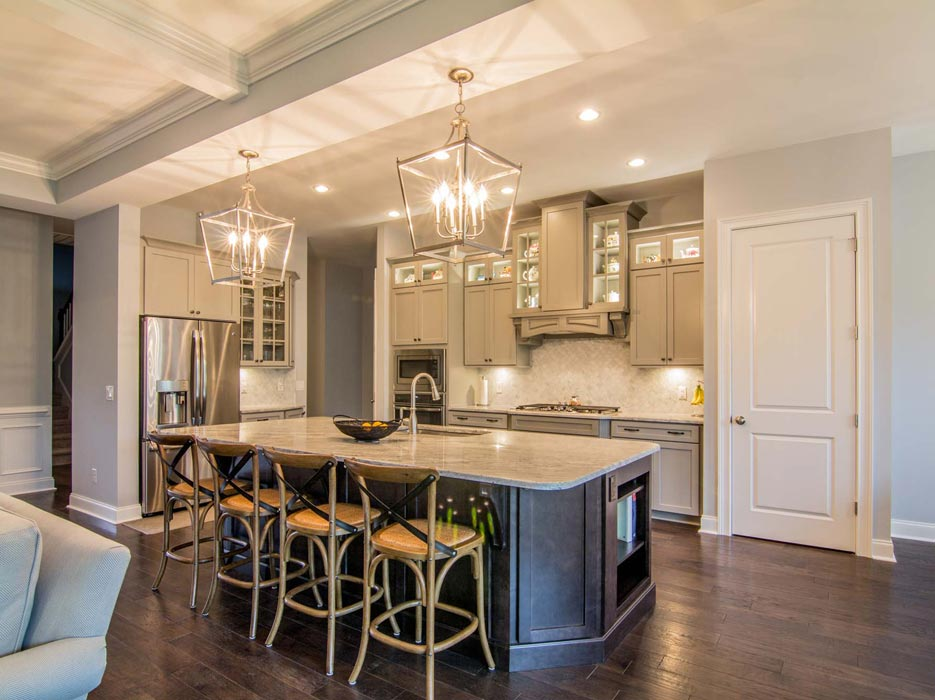 Custom cabinets frame a traditional cooking alcove, fronted by an oversize prep island and entertaining space – typical Granite Empire quality.