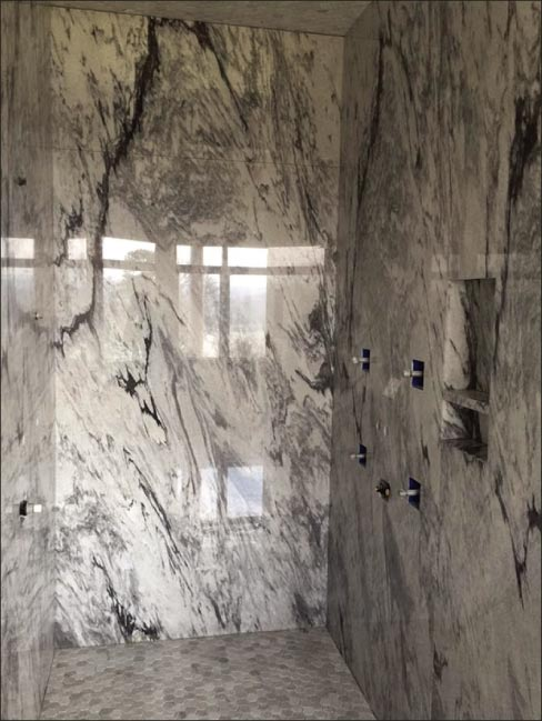 Grey Pearl marble shower, cladding sourced from Polycor, with matching octagonal mosaic floor.