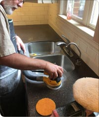 Refinishing dark Corian – starting with diamond-impregnated pads on an orbital sander, and replacing original medium gloss