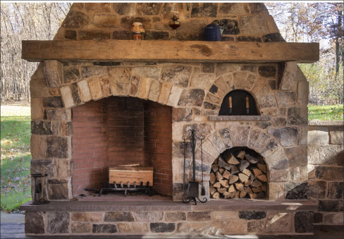 Outdoor Kitchen and entertainment area with an over-size fireplace also showcases their ashlar fieldstone construction.