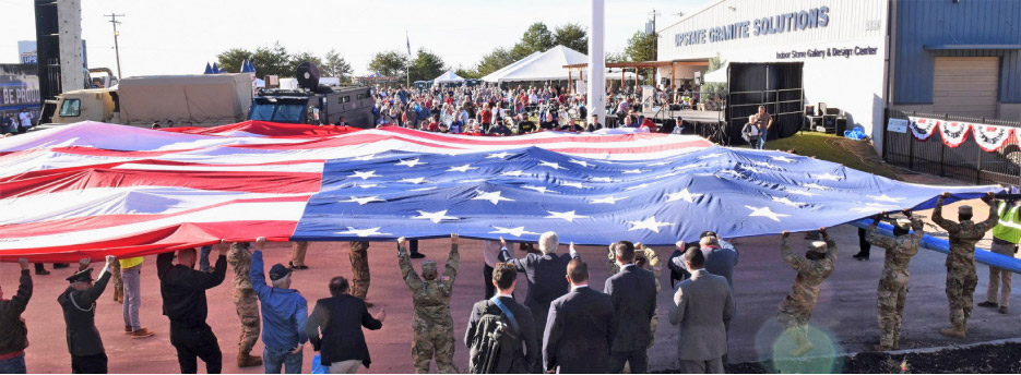 U.S. Armed Forces veterans and volunteers unfurl the giant flag in the Veteran's Day program at Upstate Granite.