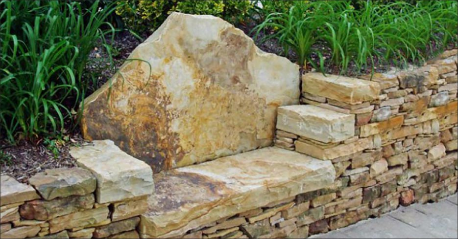 A combination retaining wall and bench made from stone remnants.