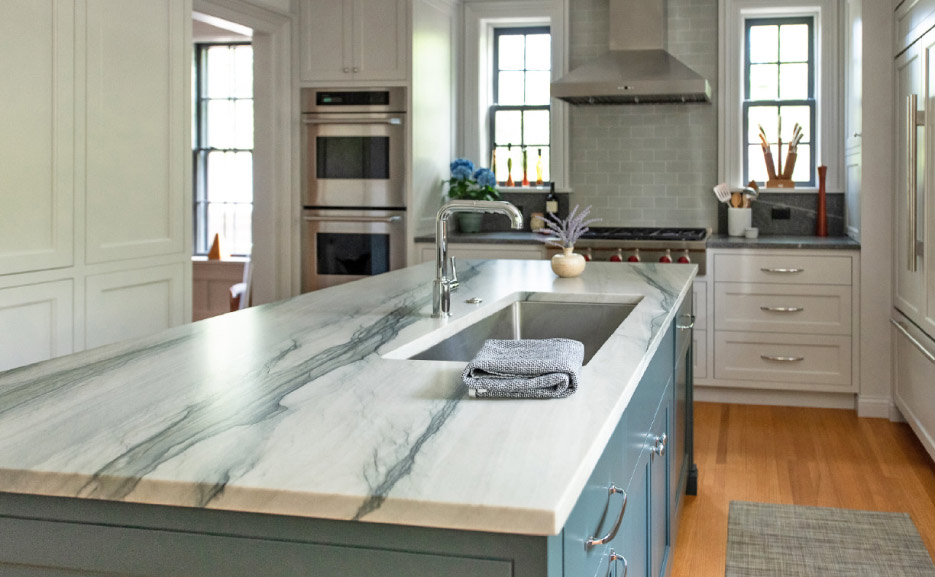 In this client's kitchen, Shumaker paired a Brazilian Calacatta quartzite with blue cabinetry. Photo courtesy Shumaker Design & Build Associates