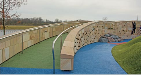 Perimeter and climbing-feature wall at the Summit Park in Blue Ash, Ohio. The rich, natural earth tones of Crab Orchard sandstone on the climbing wall is a perfect match of stone to purpose.