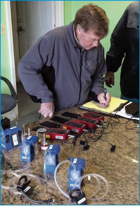 Richardson calibrating noise dosimeters and air pumps prior to shop environment testing.