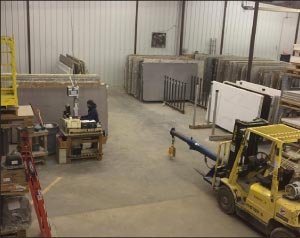 Solid Surface Designs' old slab storage system made for less free space to extract slabs from a rack, and increased forklift travel. They use a slab photo scanning and bar code system to track slab inventory, work station seen at center left.