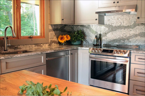 This residential kitchen features pattern and book-matched  Cambria quartz, designed to flow across the countertops and the full-height backsplash.