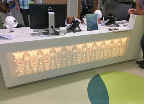 Backlit Corian desk, milled to different depths and including complex butterfly shapes, for Strong Children's Hospital