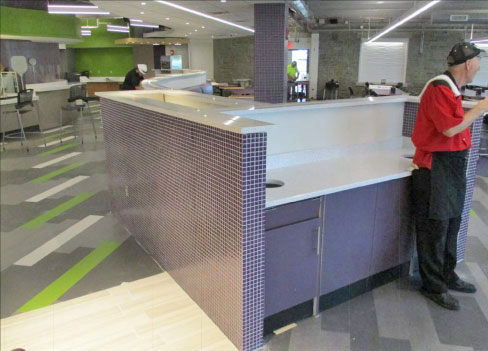 A recent Niagara University project (shown in progress) included a refit of solid surfaces throughout Clet Hall. Above and below: cafeteria installation of a long, curved bench barrier separating seating and the serving line, and the tray return area.