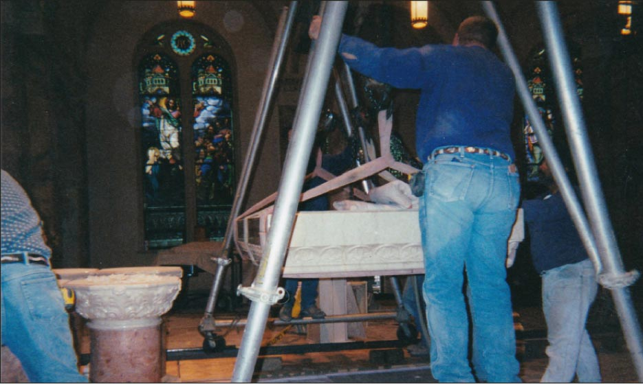 Step 8: After getting the piece into position in front of the altar and laying the piece down in the horizontal position, a rolling A-frame with a 14-inch aluminum I-beam and chainfalls were used to hoist the piece high enough to come over the top of the waiting base of four columns..Look closely and you will see that the wheels are being kept straight by a track made out of channel irons. Its important to remember this technique, as carrying such a heavy load on an A-frame support is very hard to manage and unwieldy. This task marks the end of day one of installation.