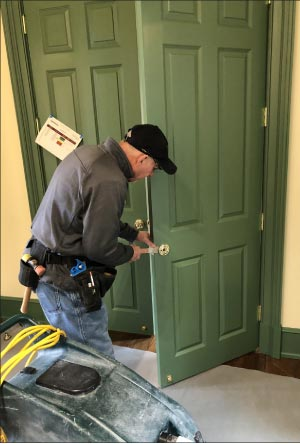 A hardware specialist installs custom fittings on these oversized doors. Note the protective drop cloth laid down to protect the new hardwood floors. Sharing construction space and cooperating with other contractors is a challenge when your area of concern is the floors, and either restoring them or preventing construction damage like stains and scratches.