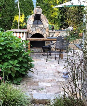 Working wood-fired fieldstone oven & rustic limestone slab tables.