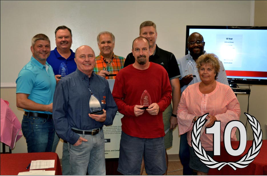 Recognized for 10 Years of Service, from left, with CEO Rick Stimac: Vice President of Development Bill Hickey, Technical Operations Charles Chesteen, CFO Dave Jester, Shipping Mike Vinyard, Warehouse Manager Ted Carver, Graphic Design William Brown, Warehouse Tammy Glass.