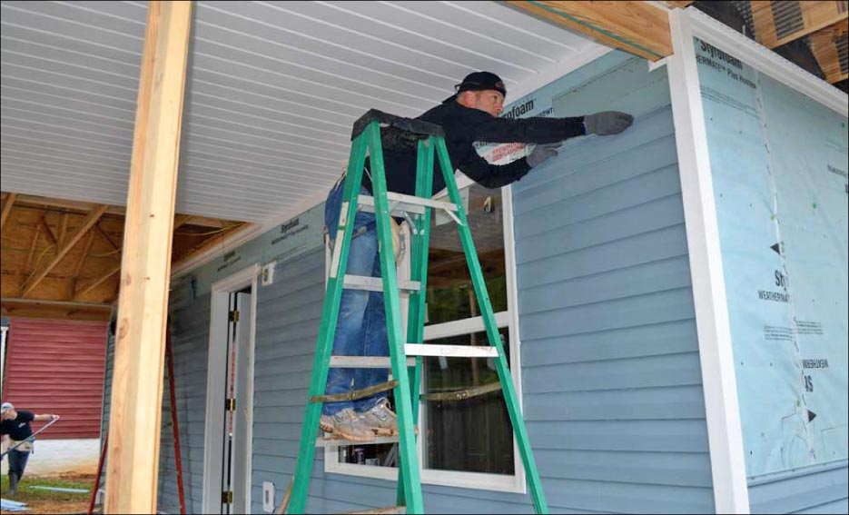 Stimac installs siding on the home.