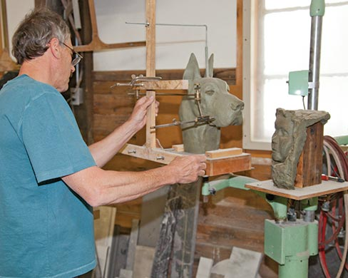 Brent Wilson, owner of Proctor Marble Company in Proctor, Vermont works with a clay model preparing to bring out the dog's head that resides within the granite.