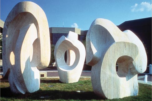 """Trilogy"" was commissioned by Glaxo, Inc., and installed at Research Triangle Park, North Carolina, located near Durham. According to Julie, ""The three pieces represented the three divisions of the company. Since they are a British company, I told them that it was my version of Stonehenge, in England. It was made from New Mexico Travertine and the pieces were quarried especially for me. All three were directly carved and took one year. This was installed in 1990 and is still my largest commission to date. However, the pieces had not been maintained for about twenty years. So, a couple of years ago, our team went over and restored the pieces to their original form."""