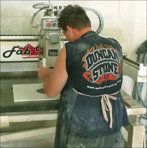 Jeremy Speegle operates the shop's Fab King with a template to make a replacement Disney fountain tile.