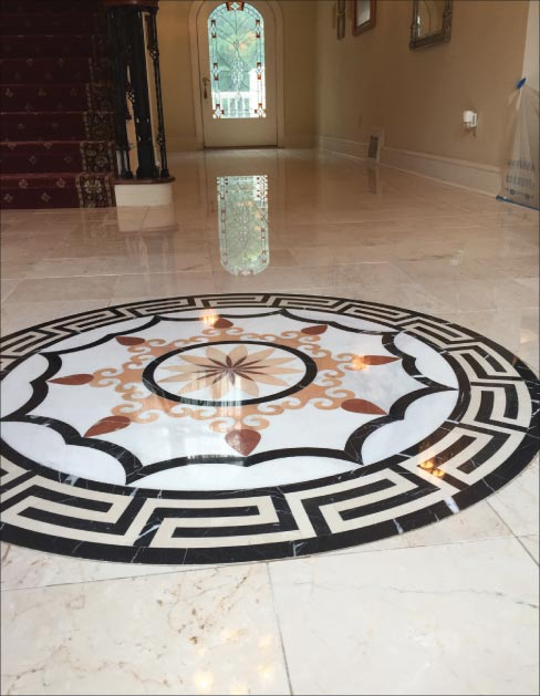 On this elaborate residential floor, eight tiles were removed and replaced where the reflection of the door is in the floor. Moderate lippage was removed and honed with a hand tool, then the entire floor was polished using the new Majestic XXX Shine Powder.