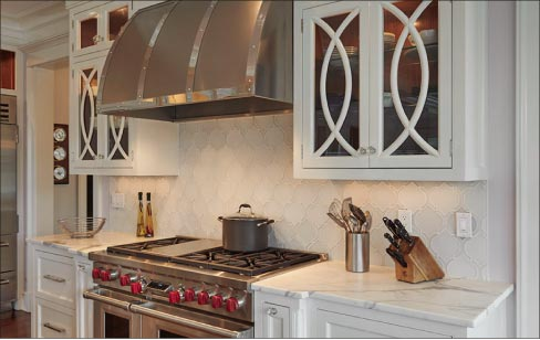 This custom marble kitchen includes matching, hourglass-shaped mosaic marble backsplash tiles.