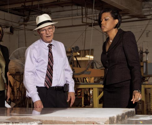 From Left: Hilgartner President Tom Doyle and Baltimore Mayor Stephanie Rawlings-Blake discuss a slab of Tennessee Cedar being polished on Hilgartner's vintage 1953 Hysaman polisher.