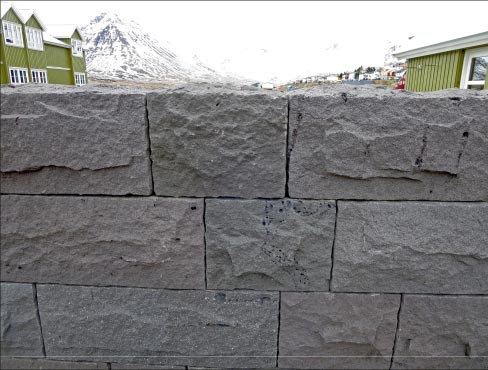 At first glance this harbor retaining wall looks like ordinary modular concrete block. But a closer inspection reveals that it's actually lava rock. The telltale sign is the presence of Swiss-cheese-like holes, caused by gases in the lava.