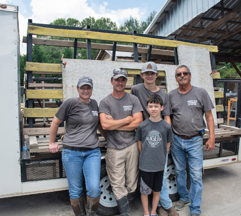 Loaded and ready to roll. Stafford built a custom trailer with an enclosed cab to hold jobsite tools and machines like his No-Lift Cart, with ample side A-frame storage to transport jobs. From left: Nina Franklin, Josh, Max and Alex Stafford, and founder Chuck Stafford.