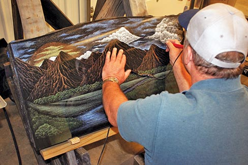 A Pyramid Marble & Granite artist hand colors an etched scene on a black granite monument