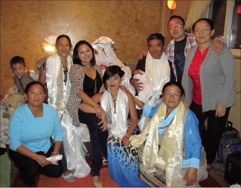 "Ngima Sherpa with his family for his twin daughters' ""Welcome to the Earth"" party in September, 2012. Sherpa is in the back row, seated with baby in hand, with her twin sister in the bassinet behind him. In front kneeling, Ngima's aunt Nuwang – his eldest daughter Tsering Sherpa in center, and his mother Ang Chokpa. Back row – Ugyen Norzang, Ngima's wife Sushma Thapa Sherpa, cousin Jazmine Ing, twin daughters Aurora and Oriana Sherpa, Ngima Sherpa, Drona Ing and Ngima's aunt Pasang Sherpa."