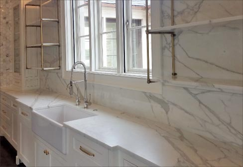 White Calacatta Borghini marble kitchen by Melissa Haynes, MH Design, features honed countertops, and includes full-height backsplashes, marble wall cladding, and even vein-matched accent shelves.