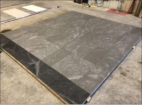 A mockup of an architectural project featuring American Mist with thermal finish. The left panel is wet to show the intense black color of the granite when enhanced.