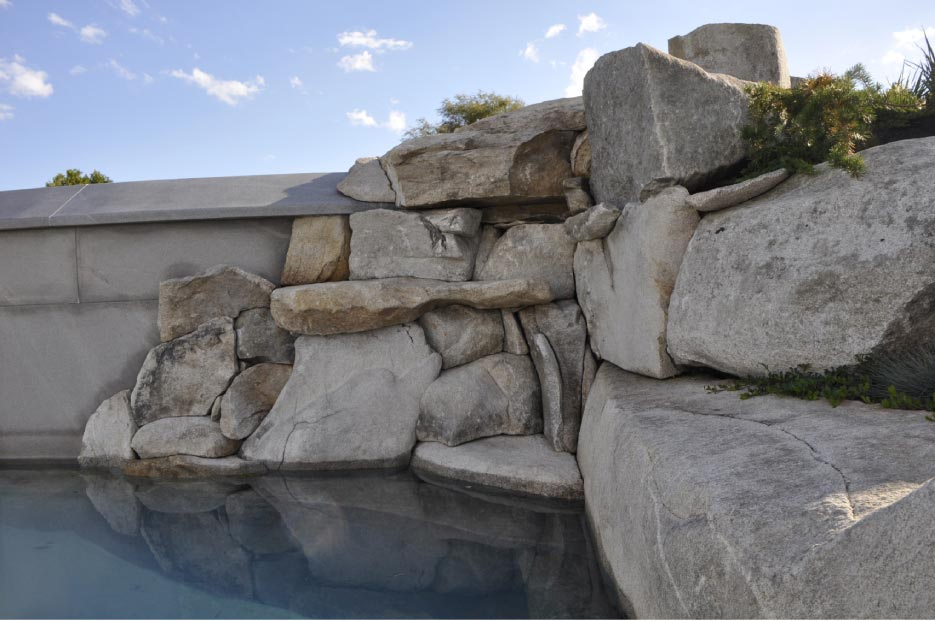 Local stone was used to create this naturalized outcropping for a waterfall and swimming pool retaining wall in Cape Elizabeth, Maine.