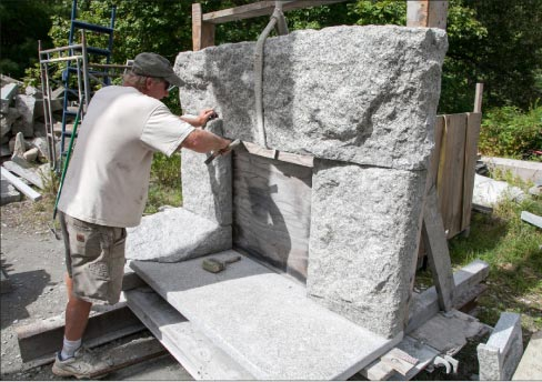 Dan Ucci shapes granite with a hand chisel, adding final touches to a fireplace surround.