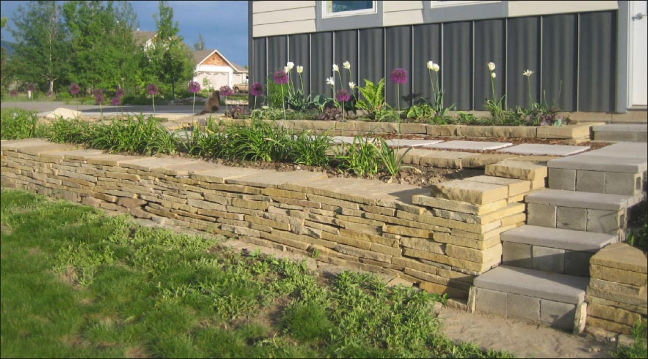Dry stone stack retaining wall and planter with capstone flags, built by Kirk.