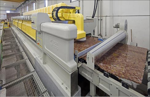 "This polishing line at a slab processing plant is applying a uniform ""factory finish"" to slabs, prior to distribution."