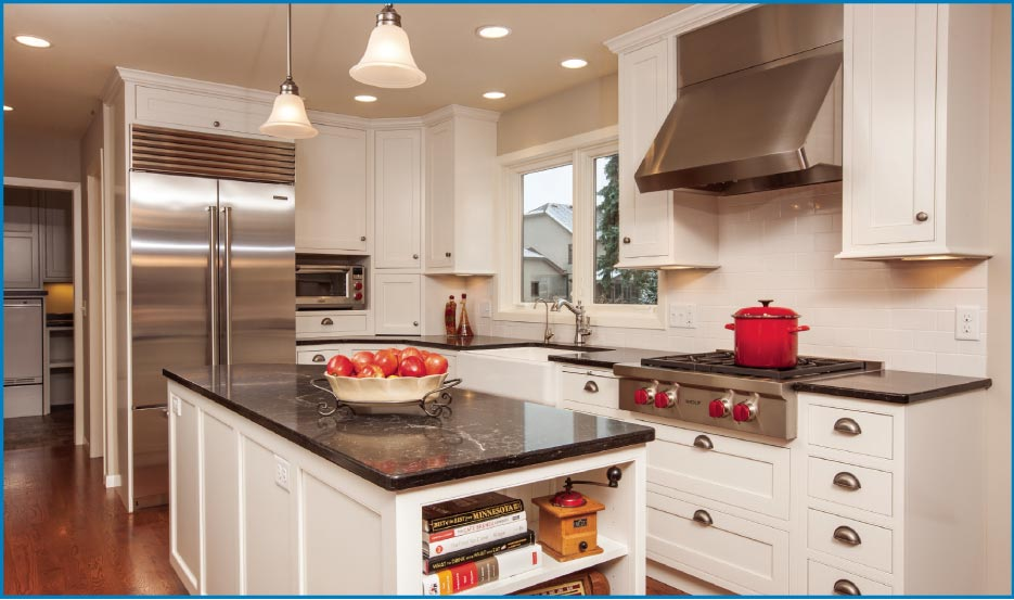 Classic white and stainless steel chef's kitchen features a large Caesarstone island and a Wolf range top.