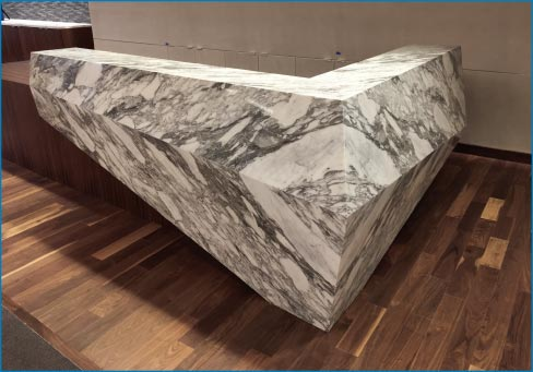 This stunning bookmatched Arabescato marble reception desk was fabricated for a law firm.