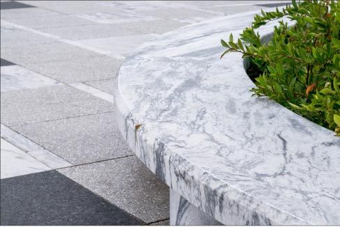 A detail perspective of a carved round Pearl Grey marble bench shows the contrast with a Laurentian Green granite paver.