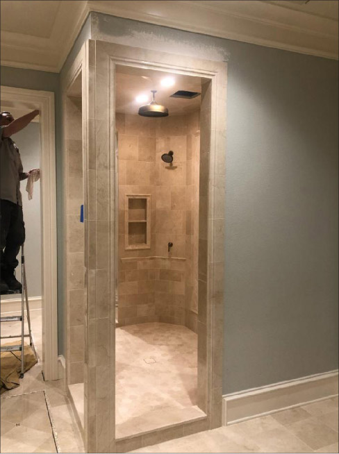 A custom Crema Marfil shower was installed in the same bathroom. All walls and columns had been flattened per industry standards before tile was installed. All resin-backed stone was primed with a single component primer suitable for wet areas and installed with minimum 95 percent mortar coverage per industry standards. Photo courtesy Stoneman Construction LLC, Portland, Oregon.