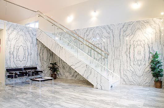 """Book matched"" is the theme for this eye-popping stairway made of Montclair Danby. Tough and durable, Vermont Danby marble is suitable for a myriad of applications from residential to commercial"