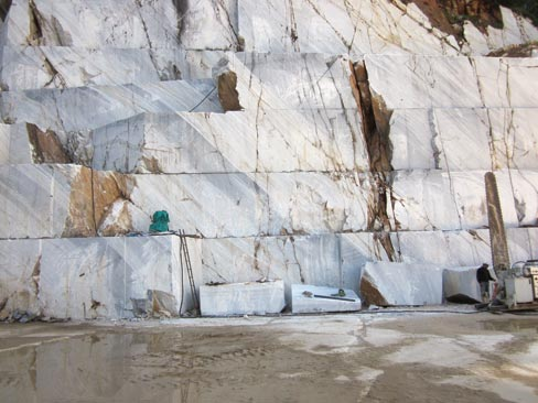 At far right, a diamond wire saw arm stands poised and ready for its next cut as the benches of blocks are dropped in this Cremo Delicato marble quarry in Carrara.