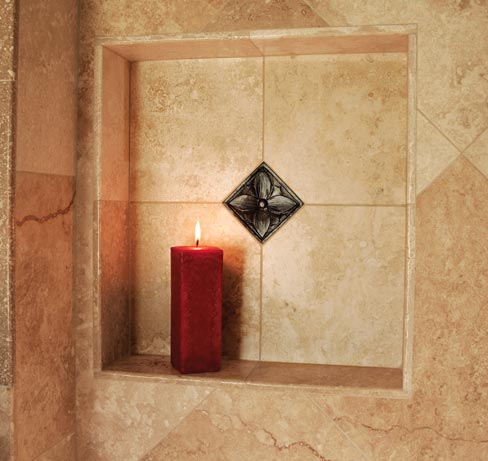 The understated elegance of a simple, oil-rubbed brass finish dot in a classical design adds warmth to a travertine tile shower niche.
