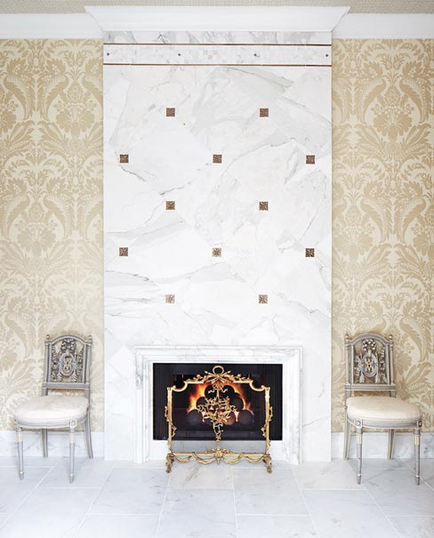 This towering Calcutta marble fireplace in a private residence is actually located in the master bath.  Designed by Landy Gardner Interiors, the fireplace stretches to the ceiling, with matching baseboards.