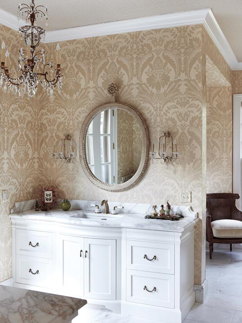 The master bath also includes vanity tops and backsplashes in Calcutta marble matching the fireplace, with classic refined details in the edging.  Photos by Matt Harrington
