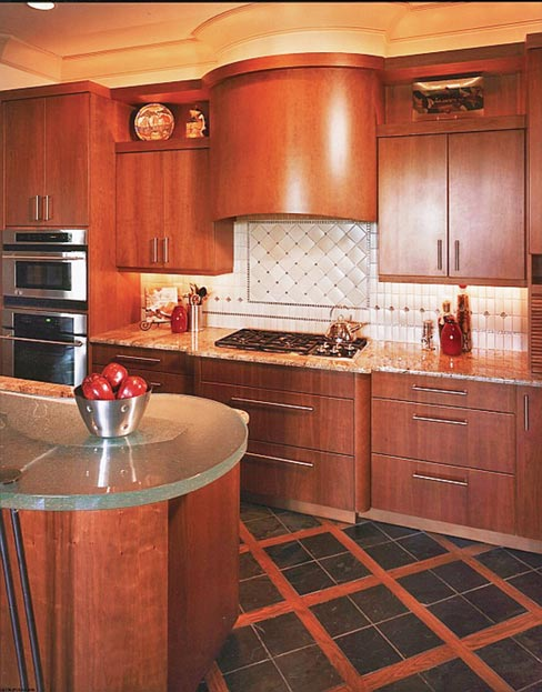 Custom kitchen produced for a country music star in 2005 includes a two-level island topped with a glass counter, curved and shaped to harmonize with the custom cabinetry and woodwork.