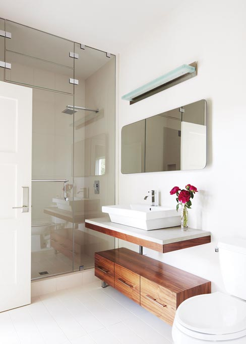 The clean, modern lines of this guest bathroom created for the Greenbaum residence features a contemporary floating vanity using Ambrosia White Granite. Photography by Matt Harrington