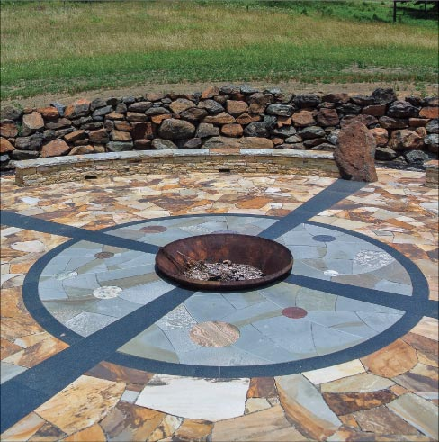 Tennessee sandstone walls and flagstone frame the ceremonial area, closest to the fire pit. Absolute Black granite rays lead towards the center, where colorful planets of stone float in a Pennsylvania Bluestone matrix.